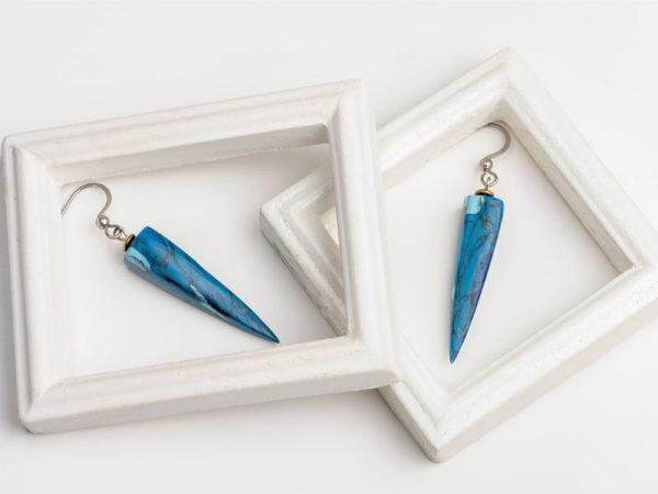Légères et élégantes les boucles d'oreilles Ursula ont une forme de pyramide et un motif pierre de turquoise les crochets d'oreilles sont en acier inoxydable de bijouterie argenté