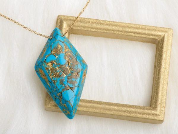 Le collier Ellen a une forme de losange avec des arêtes biseautées et présente un recto avec une magnifique imitation de la pierre de turquoise symbole d'équilibre de positivité et de sérénité un véritable art bijou