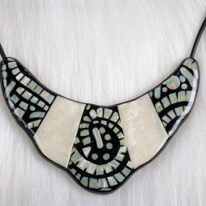 Le collier Indira est modulable il est réversible et réglable en longueur sur son recto on retrouve un superbe assemblage d'imitation nacre et de mosaïque ses finitions en font un produit de bijouterie de luxe