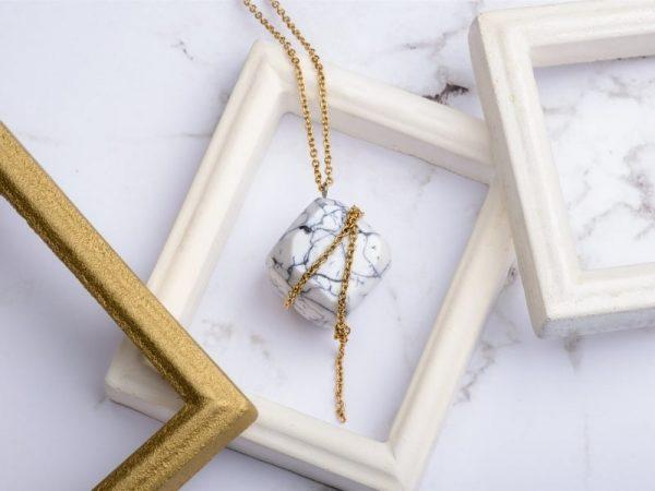 Com'une Alchimie vous présente le collier luxe Olympe en imitation marbre blanc et de forme cube une fine chaîne dorée en acier inoxydable de bijouterie vient parfaite cet élégant pendentif