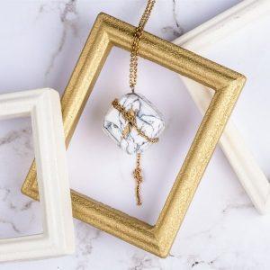 Au dos du collier luxe Olympe vous retrouverez en plus de l'imitation marbre blanc et de la chaîne dorée l'emblème de Com'une Alchimie le phénix doré